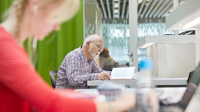 Eine Frau und ein Mann arbeiten in der Bibliothek der Universität Luzern.