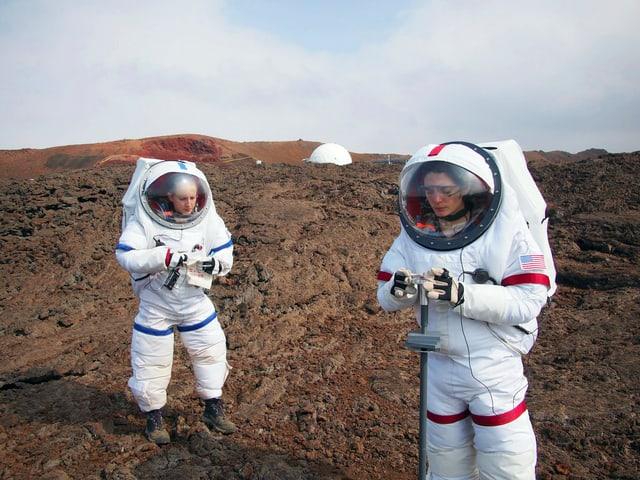 Zwei Forscher im Raumanzug auf der Vulkanoberfläche.