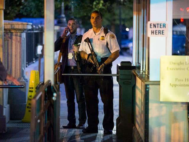 Bewaffnete Agenten vor einem Drehkreuz