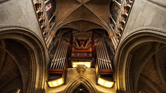 Beleuchtete Kirchenorgel in einer Kathedrale.
