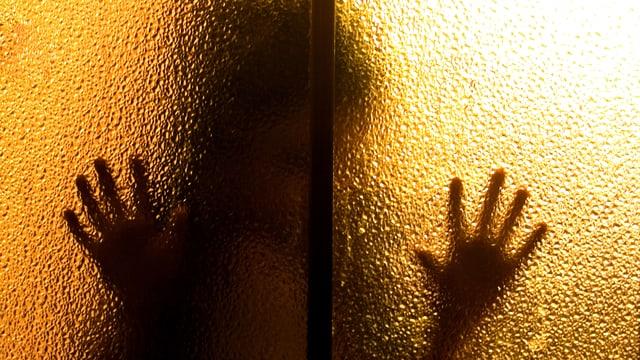 Eine dunkle Silhouette vor einem gelb beleuchteten Fensterglas.