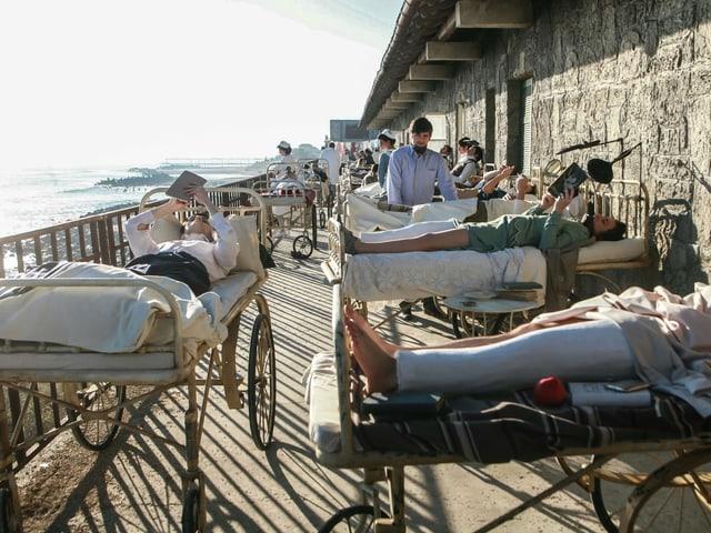 Ein paar Menschen liegen in Krankenbetten auf einer Terrasse, die das Meer überblickt.