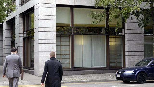 Fassade der BKB-Filiale in Zürich. Vor dem Gebäude sind zwei Männer von hinten zu sehen, die gerade die Strasse überqueren.