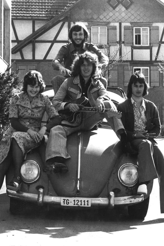 vier Männer in rockiger Aufmachung sitzen auf einem VW Käfer.