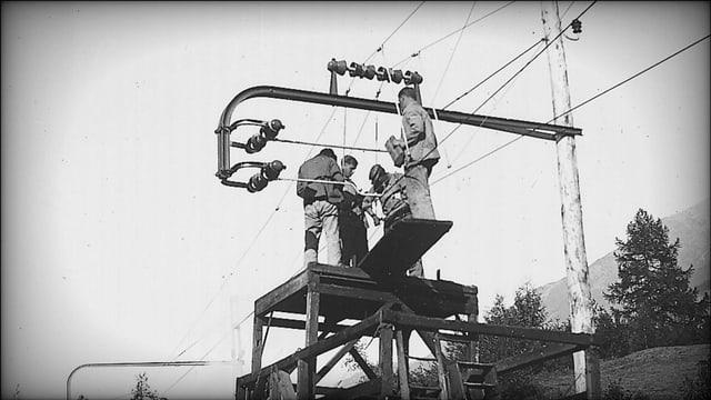 Vier Männer auf einer Archivaufnahme, die eine Leitung der Berninabahn montieren.