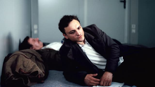 Franz Rogowski als sinnierender Flüchtlich auf einem Bett.