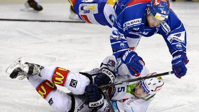 Ein Eishockeyspieler am Boden, einer in der Luft.