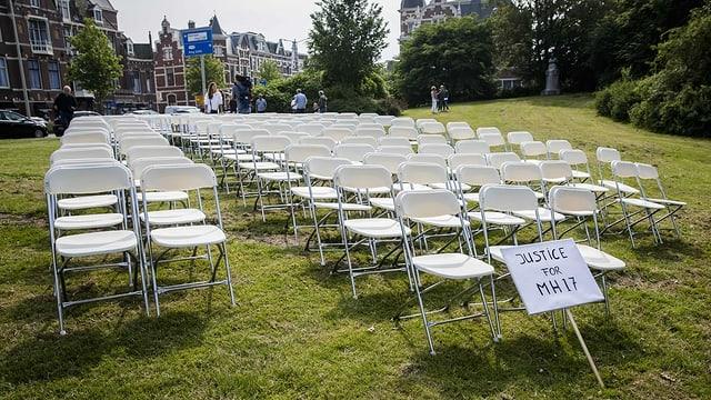 Weisse Stühle stehen, aufgereiht wie in einem Flugzeug, auf einer Rasenfläche.