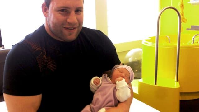 Adi Laimbacher mit einem Baby im Arm.