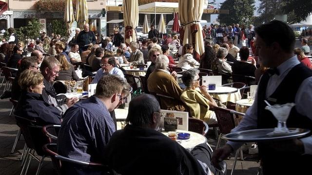Service-Fachmann, Restaurant-Gäste im freien an Tischen sitzend.
