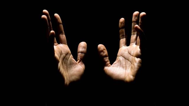 Zwei männliche Hände strecken vor scharzem Hintergrund gegen oben.