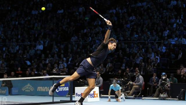 Roger Federer spielt einen hohen Ball mit einem spektakulären Rückhand-Volley ins Feld zurück.