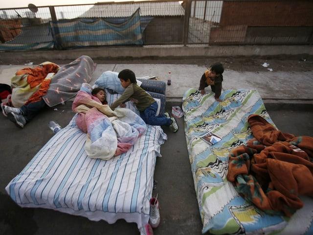 Kinder auf Matratzen, die auf der Strasse liegen.
