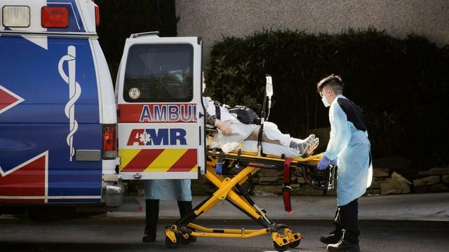 Ein Patient wird in eine Ambulanz geladen, die Nothelfer tragen Gesichtsschutz und Schutzkleidung.