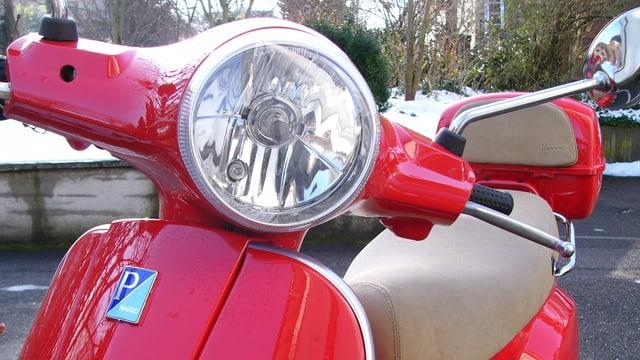 Ein roter Roller steht auf einem Parkplatz.