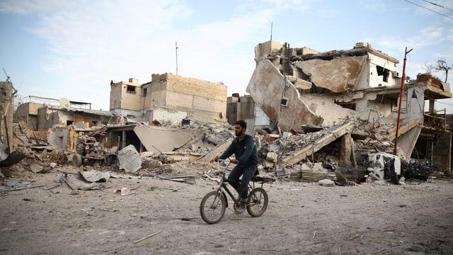Mann fährt auf Velo an zerstörten Häusern vorbei