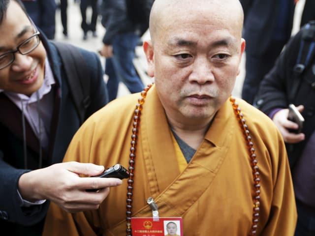 Shi Yongxin in Mönchskleidung, ein Mann hält ihm ein Aufnahmegerät hin.