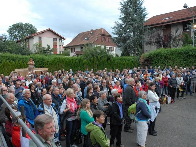 Publikum steht im Freilichttheater, das von Thujahecken umgeben ist.