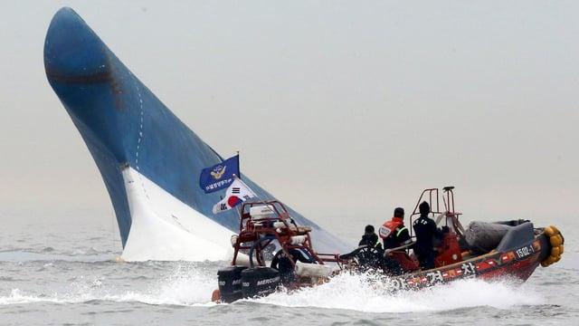 Die Spitze der Fähre ragt aus den Fluten, ein Boot umfährt das Wrack.
