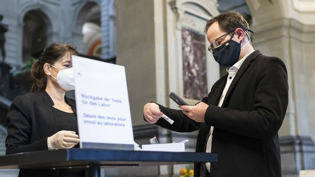 Nationalrat der Grünen Balthasar Glättli registriert seinen Covid-19 Test, bevor er ihn der Mitarbeiterin der Parlamentsdienste, Agathe Casutt gibt.