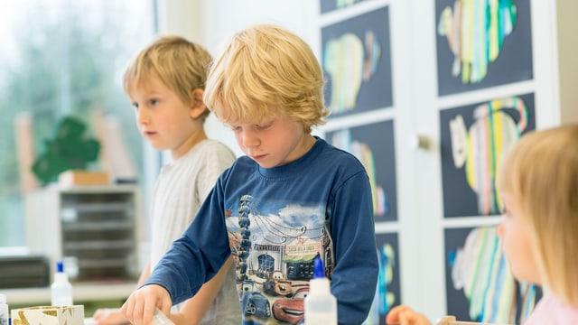 Drei Kindergartenkinder basteln