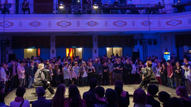 Zwei Akkordeonisten sitzen sich gegenüber, umgeben von stehendem Publikum.
