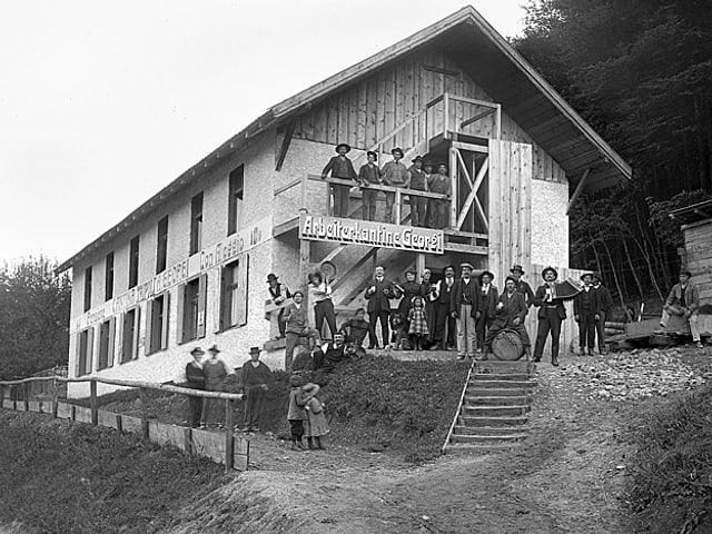 Arbeiterfamilien posieren vor einer Wohnbaracke.