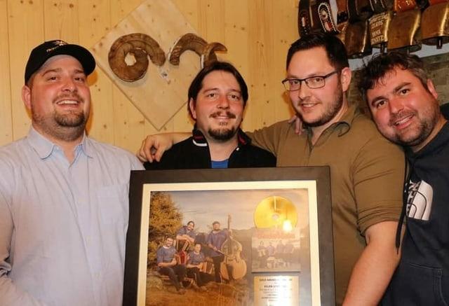 Vier Männer halten eingerahmte Goldene Schallplatte in Händen.