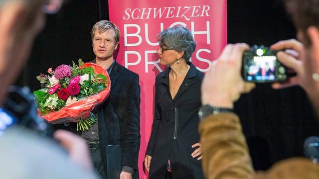 Ein Mann mit einem Blumenstrauss in der Hand, daneben eine Frau.