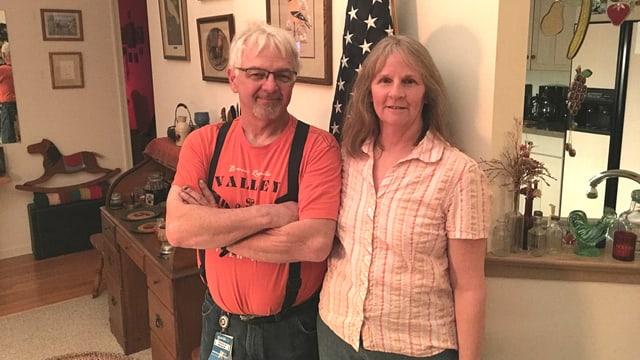 Ein Mann und eine Frau stehen in einer Wohnung und blicken in die Kamera.