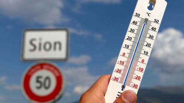 Handgehaltenes Thermometer zeigt 44 Grad.