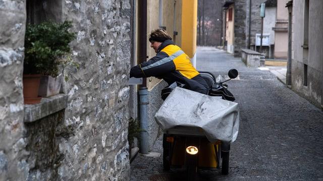 Pöstlerin in einem Dorf mit ihrem Moped unterwegs.