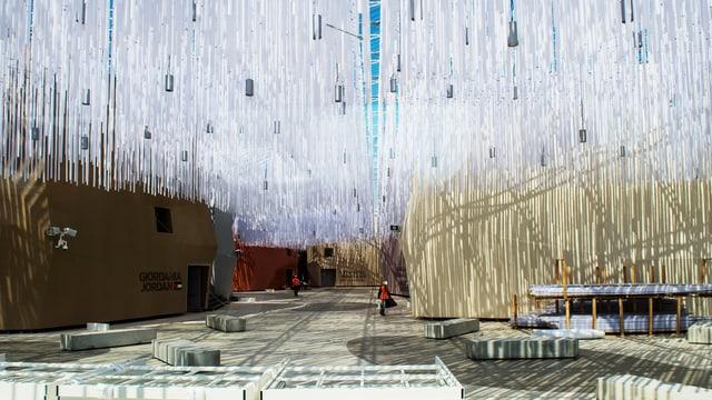 Weisse Fäden hängen von der Decke. Daneben steht der grün-braune Pavillon von Jordanien.