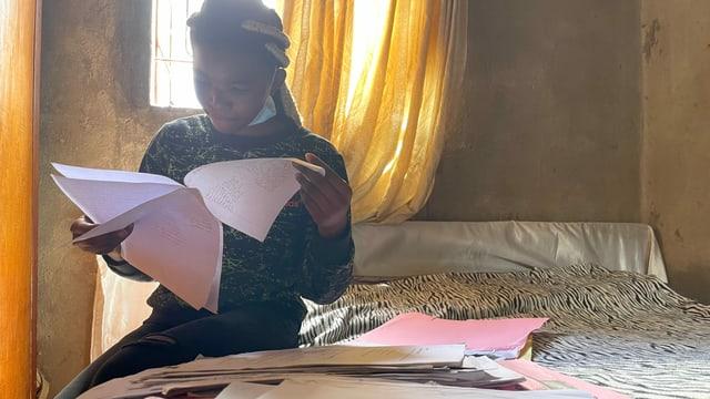 Mädchen mit schriftlichen Unterlagen sitzt auf Bett