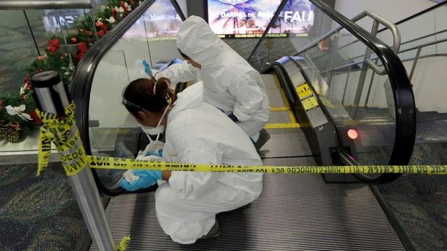 Zwei weiss gekleidete Menschen putzen die Rolltreppe am Flughafen. Absperrband.