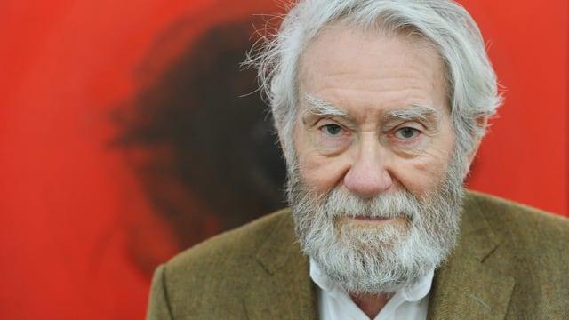 Porträt von Otto Piene vor rotem Hintergrund.