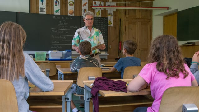 Il scolast davant che instruescha ina gruppa d'uffants.