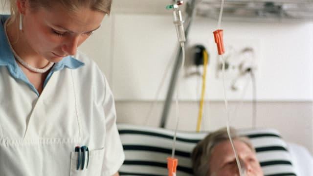 Krankenschwester im Spital, daneben Patientin im bett