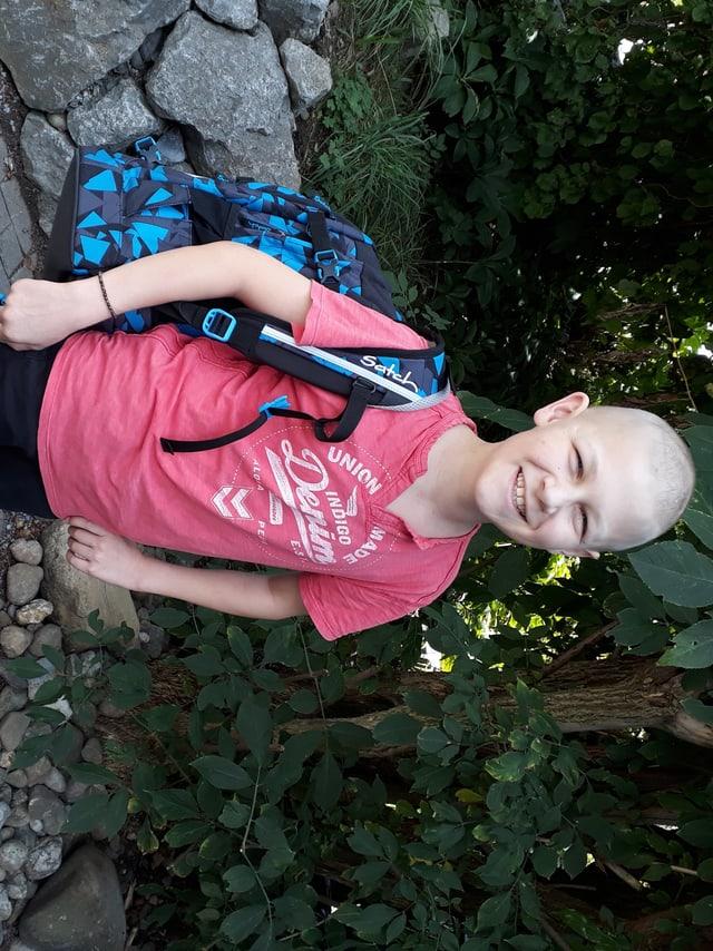 Mattia lächelt in die Kamera, über seiner rechten Schulter hängt ein blauer Rucksack und im Hintergrund sind Sträucher und Pflanzen.