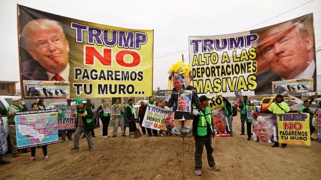 Plakate mit Trumps Antlitz und Parolen.