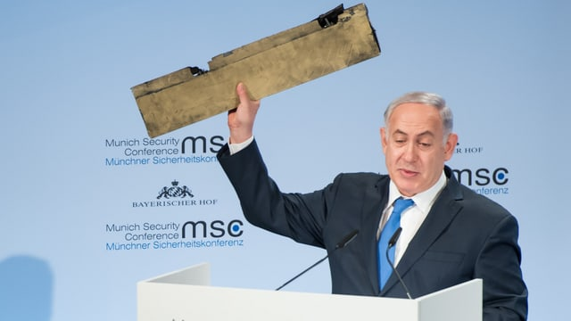 Netanjahu ein Trümmerteil in den Händen haltend.