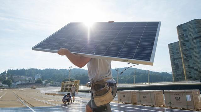 In lavurant cun in panel solar sin in tetg.