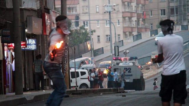 Demonstranten werfen einen Molotow-Cocktail in Richtung Polizei in Diyarbakir