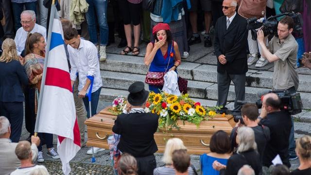 Menschenmenge um den Sarg von Dimitri, eine Clownin wirft eine Kusshand zu