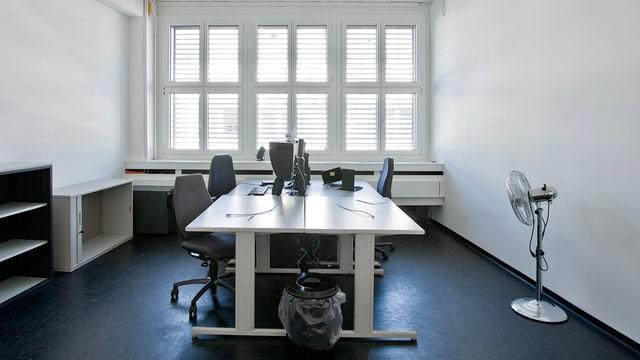 Ein ziemlich leeres Büro mit Ventilator, Tisch, Stühlen und Abfalleimer.