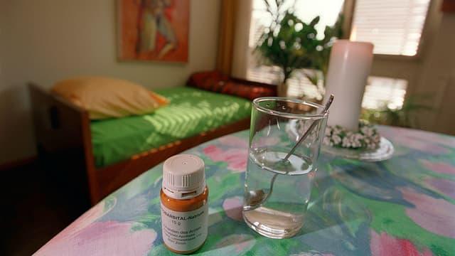 Löffel, Glas und Pentobarbital-Natrium auf Tisch stehend. Im Hintergrund ist ein Bett erkennbar