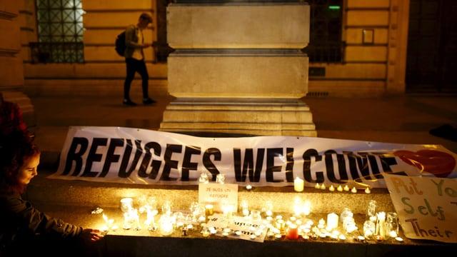 Kerzen brennen in der Nacht auf dem Trottoir, dahinter ein Transparent, auf dem steht: Refugees Welcome.