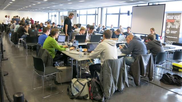 In einem Sitzungsraum sitzen viele junge Hacker an ihren Laptops.