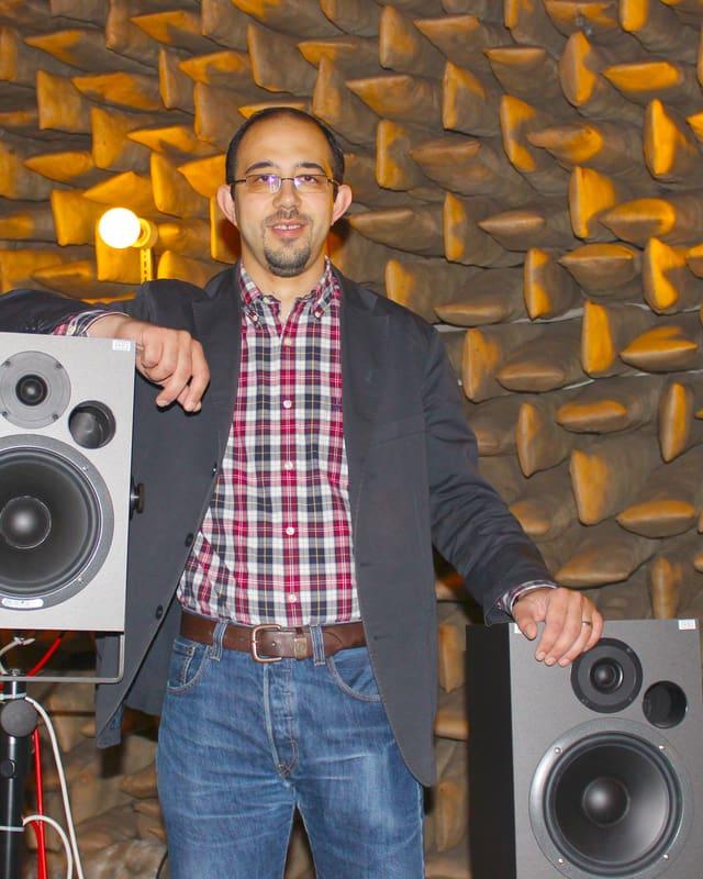 Ein Portrait von Ercan Altinsoy, der zwischen zwei Lautsprechern steht.