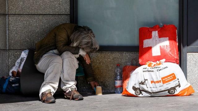 Ein obdachloser Mensch mit seinen Tüten sitzt vor einer Hausmauer.